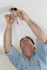 Qualified Electrician Installing Lighting Fixture