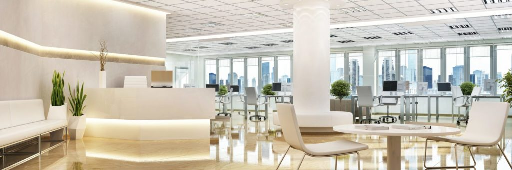 White open concept office space with white couches and chairs and LED lighting