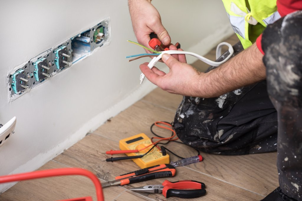 Electrician fixing electrical code violations